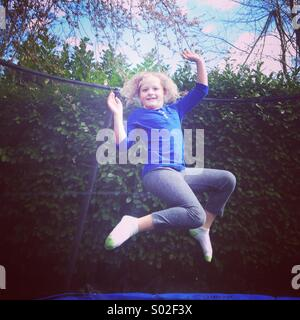 Girl, aged 9, jumping on trampoline. - Stock Photo