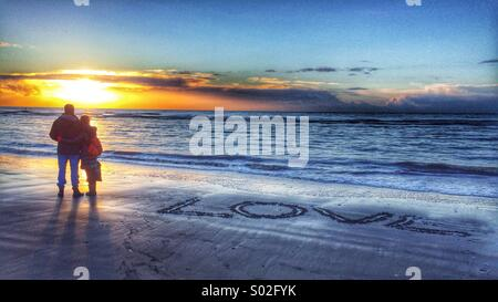 A couple stand at the shore watching the sunset the word Love inscribed into the sand next to them - Stock Photo