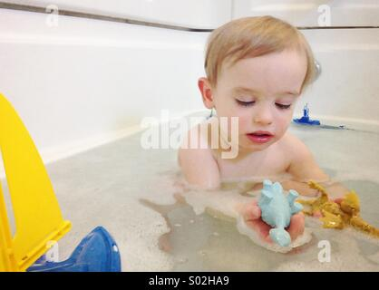 Toddler boy playing with toy dinosaurs in bath - Stock Photo