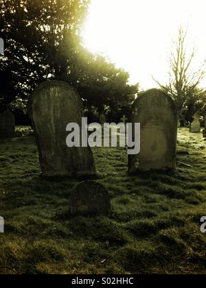 Old family of grave headstones in a rural church yard - Stock Photo