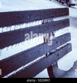 Icicles on park bench in freezing rain and snow - Stock Photo