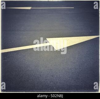 Painted opposite white arrow sign on asphalt - Stock Photo