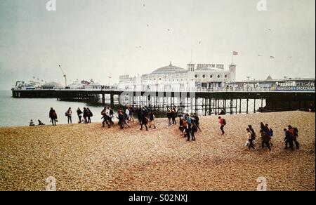Royal Pier, Brighton, East Sussex, England, group of young people walking along the beach - Stock Photo