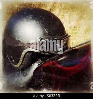 Old tatty and grungy open faced crash helmet and goggles resting on the seat of a motorcycle the helmet is very - Stock Photo