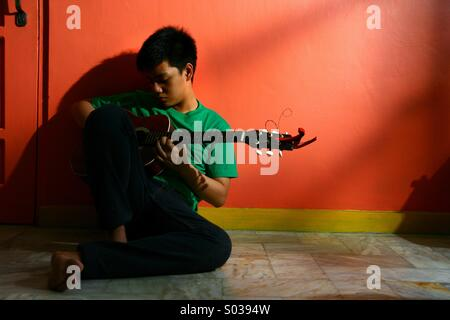 Young asian teen playing guitar in an empty living room - Stock Photo