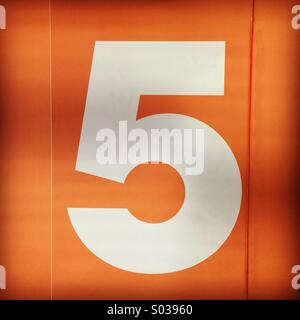 White number five floor number on an orange background. - Stock Photo