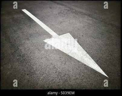 Painted white arrow sign on asphalt - Stock Photo
