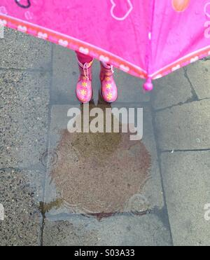 Child in pink gumboots standing in the puddle - Stock Photo