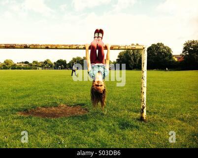 Girl hanging upside down - Stock Photo