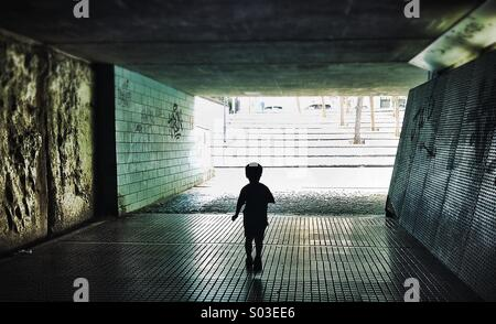 Silhouette of a person walking through a dark underpass symbolizing light at the end of the tunnel - Stock Photo