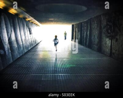 Silhouettes walking through a dark under pass simbolizing light at the end of the tunnel - Stock Photo