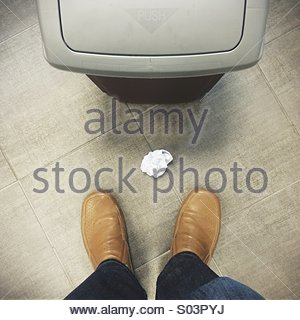 Man standing next to rubbish bin and crumpled piece of paper - Stock Photo