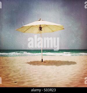 A single umbrella on the beach. Abu Dhabi, U.A.E. - Stock Photo