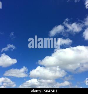 Blue sky and fluffy white clouds can be used for background with space for text - Stock Photo