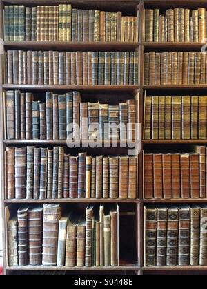 Old bookcase full of leather bound books - Stock Photo