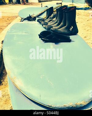 Wet shoes of different sizes lie on surfboard on Polzeath beach in Cornwall - Stock Photo
