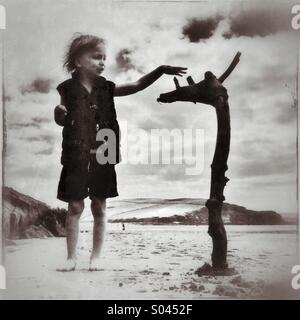 Boy and flotsam on Bigbury beach in Devon - Stock Photo
