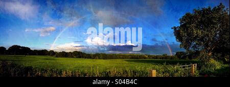 Full rainbow over countryside - Stock Photo