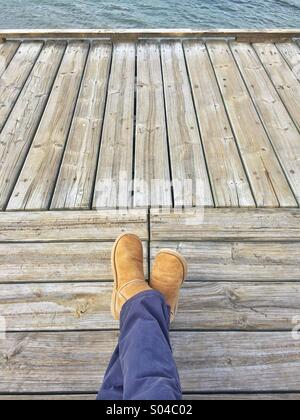Relaxed legs crossed on wood deck looking towards Water - Stock Photo