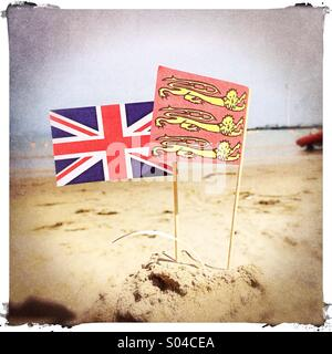 Flags on a sandcastle on the beach, UK - Stock Photo
