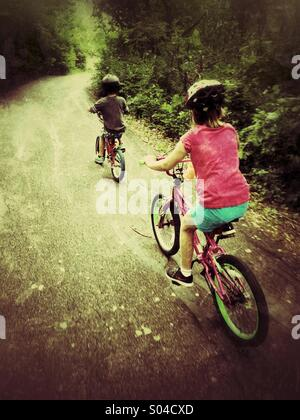 Two children ride their bicycles on a path through the woods. - Stock Photo