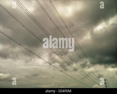Electricity power lines and grey sky. - Stock Photo
