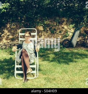 Young woman sitting on back yard lawn chair in sunshine - Stock Photo
