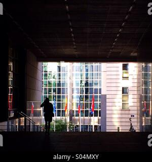 Silhouetted figure outside European Parliament building, Brussels - Stock Photo