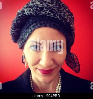 Woman wearing head scarf against red wall - Stock Photo