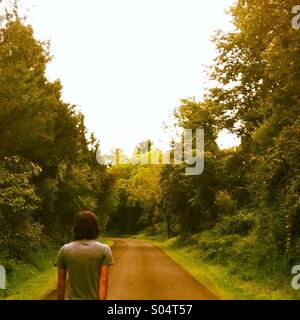 A young man walks down a narrow lane surrounded by trees. - Stock Photo