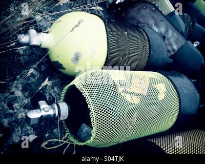 Scuba diving aqualung air tanks lying on rocks. - Stock Photo