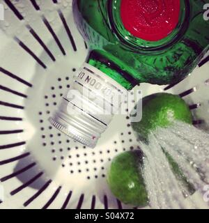 Green bottle of gin next to limes being washed with a stream if water while sitting in a colander. - Stock Photo
