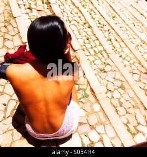 Girl sitting on stone steps, Portugal - Stock Photo