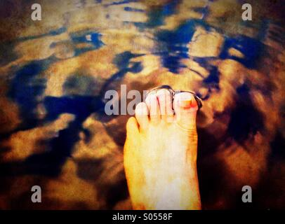 Dipping foot to a lake - Stock Photo