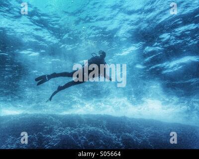 Scuba diver in surf - Stock Photo