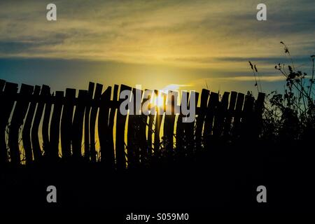 Crooked silhouetted fence - Stock Photo
