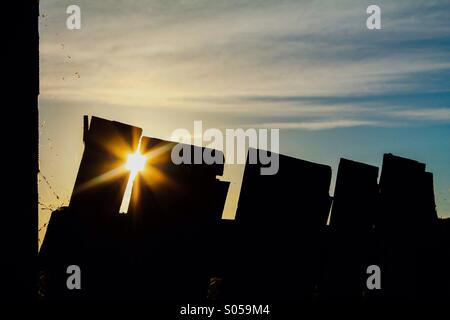 Crooked fence and sun flare - Stock Photo