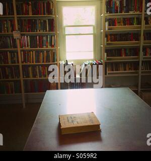 One book Ina table in a sunlit library room - Stock Photo