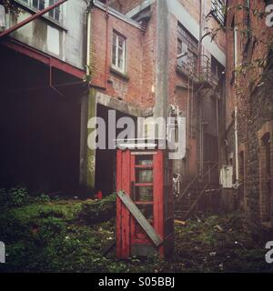 Defunct telephone booth abandoned in a courtyard - Stock Photo