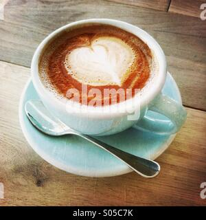 A cup of latte/cafe mocha with a heart shaped on the top. - Stock Photo