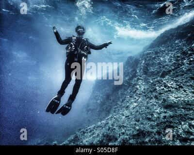 Scuba diver floating in mid water over a limestone reef. - Stock Photo