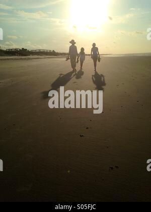The silhouettes of three people walk along the beach in morning light. - Stock Photo