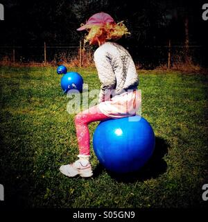 Young girl bouncing on space hopper - Stock Photo