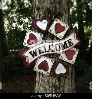 Welcome sign on a tree. - Stock Photo