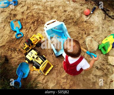 Toddler boy plays with a shovel and trucks in a large sandbox. - Stock Photo