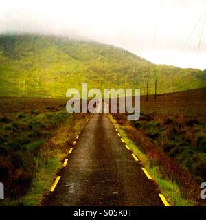 A road with no cars on it leading into the mountains. Co Kerry, Ireland - Stock Photo
