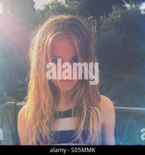 Portrait of girl thirteen blonde backlit by the evening sun - Stock Photo