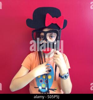 Silly kid wears fake glasses and a mustache against a red wall. - Stock Photo