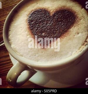 Cappuccino coffee drink in large mug and a heart shaped chocolate shape on the foam - Stock Photo