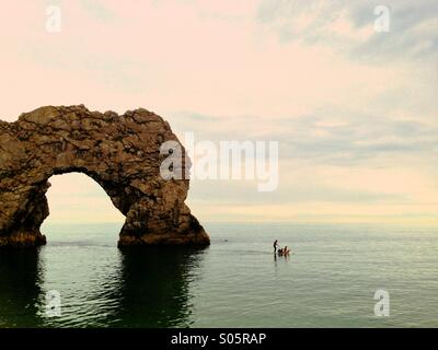 A family enjoy the sea on a paddle board at Durdle Door Beach, Lulworth Estate, West Dorset. - Stock Photo
